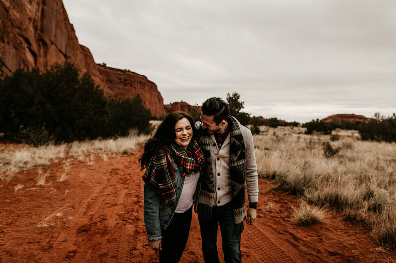 engaged couple holding each other and walking along red rocks