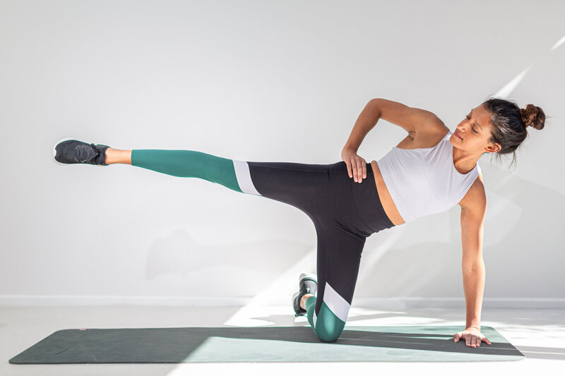Postpartum woman in assisted side plank
