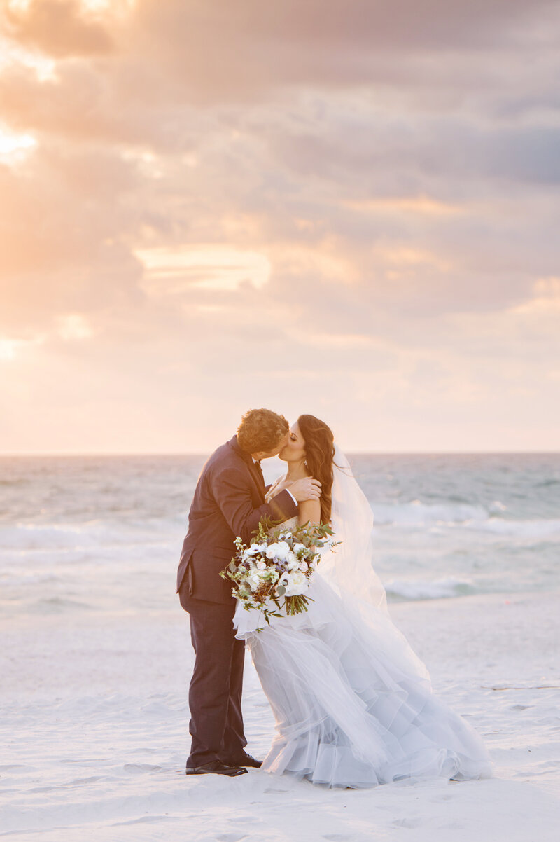A bride and groom kiss passionately on a beach at sunset. They just had a micro wedding package in Florida with Intimate Weddings 30A