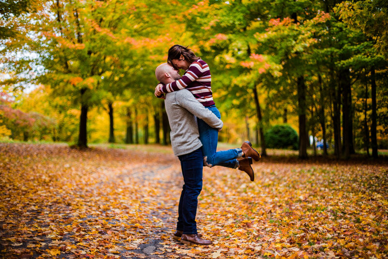 Man lifts fiancee and smiles at her during engagement photos in Girard PA