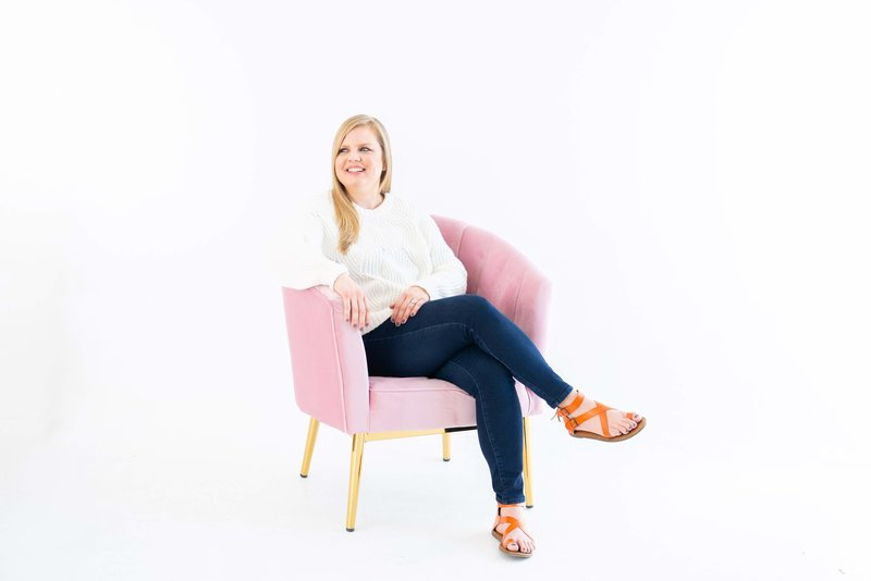 Blonde woman wearing a white sweater sitting in a pink chair