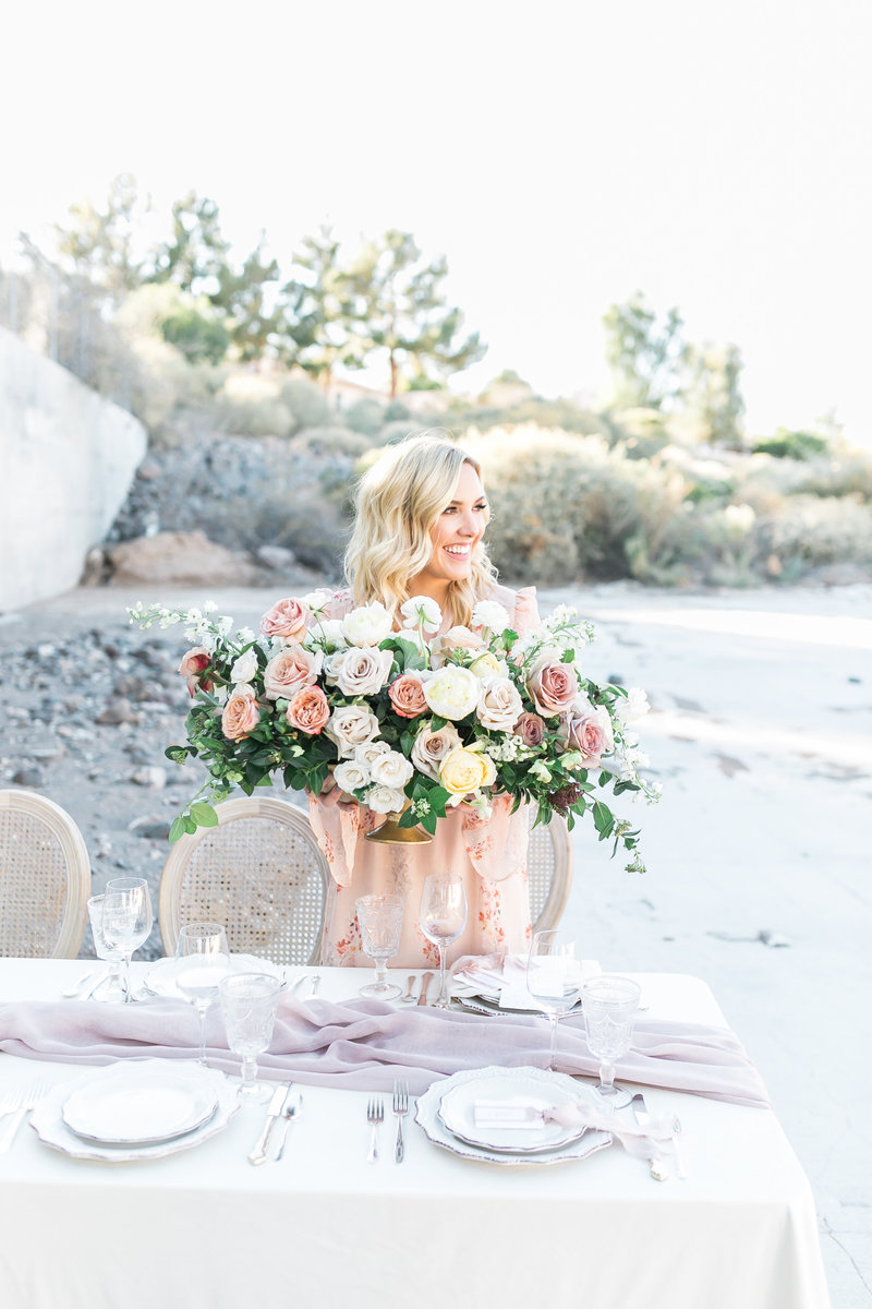 Ashley Thompson of Ashley Creative Weddings & Events designing a tablescape while holding a bouquet of roses