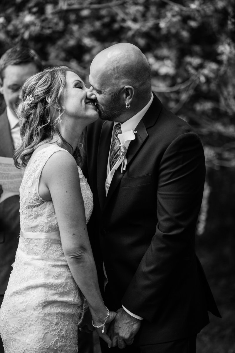 Bride and groom share first kiss in backyard wedding ceremony in Erie, PA