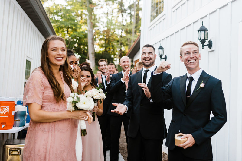 wedding party cheers while bride and groom out of frame share a kiss after their wedding ceremony at historic rosemont springs in berryville virginia