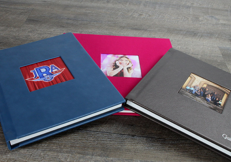 three photo albums with image cut out in cover