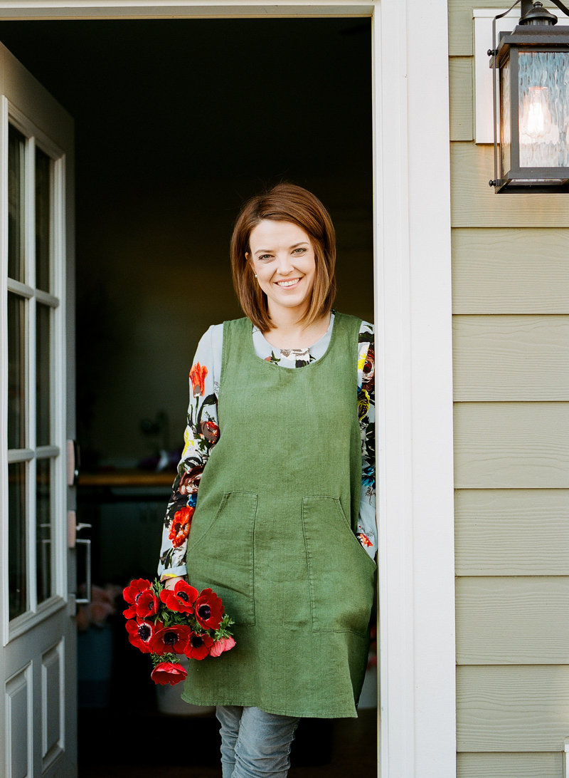 Emily Kennedy, floral designer, leans on doorframe holding red bouquet