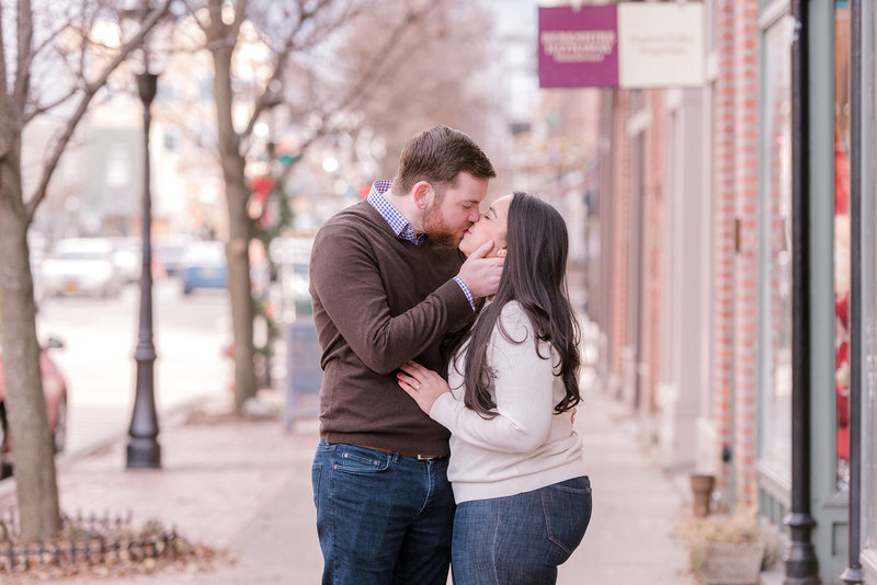 engaged couple share a moment on the sidewalk
