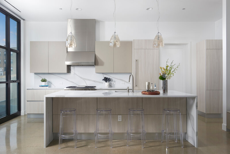 Washington Kitchen white marble countertops with beige wood cabinetry clear acrylic bar stools greenery in a chrome vase and natural wood tray