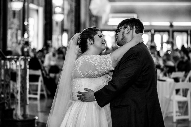 Bride and groom smile at each other during first dance at Warner Theatre wedding
