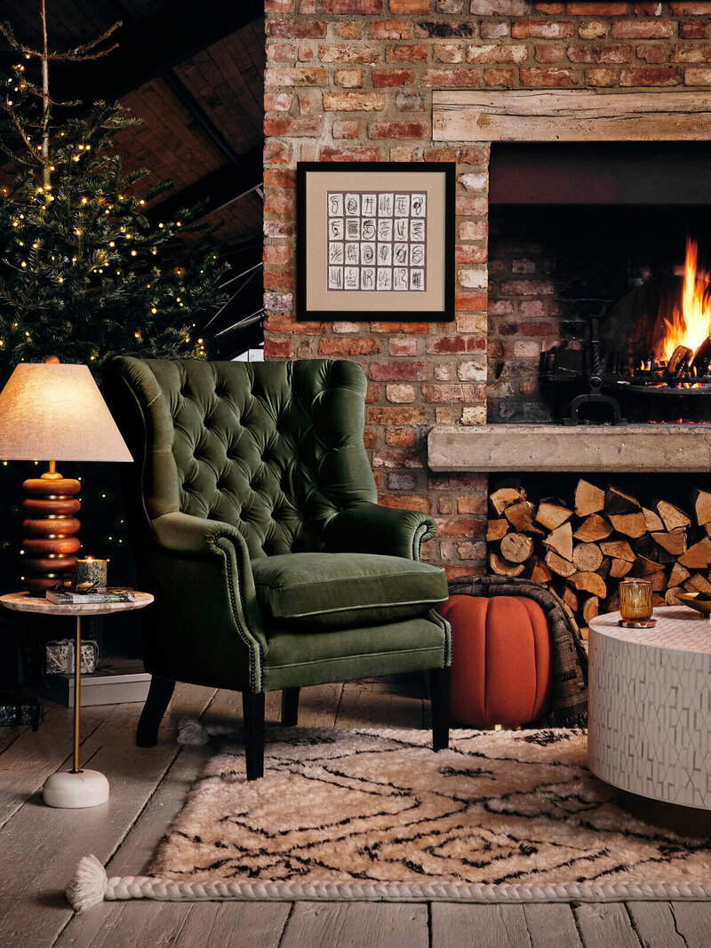 A Soho Home velvet moss green chair is pictured next to a brick fireplace on a rug.