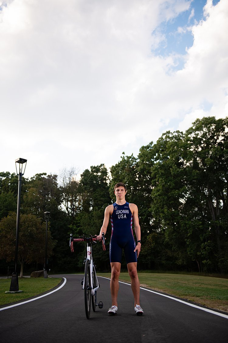 High school senior boy in USA bike suit standing beside bike on curved paved road with blue skies at Hartwood Acres in Pittsburgh, PA
