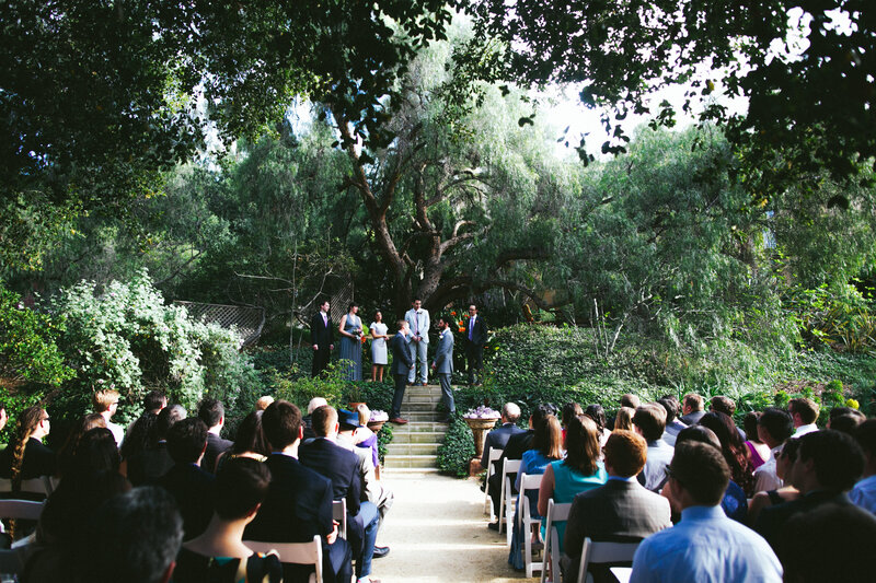 Same sex couple takes their wedding vows under beautiful tree in outdoor wedding ceremony