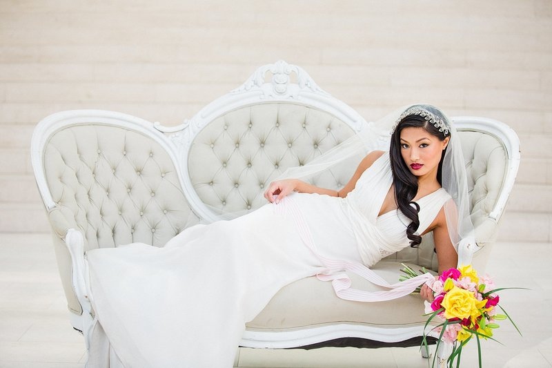 A bride lays on a vintage settee.