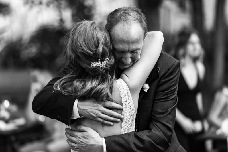 Father hugs daughter as he gives her away at her intimate backyard wedding