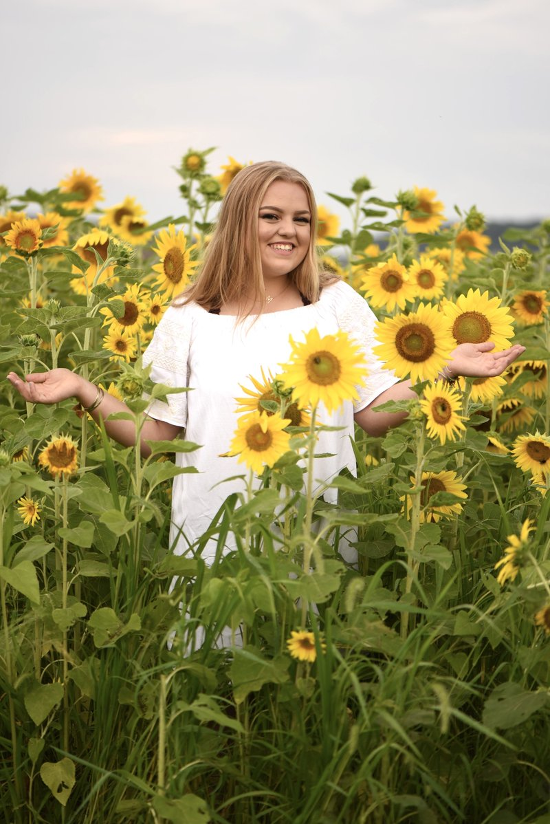 Senior girl in white dress in sunflower field