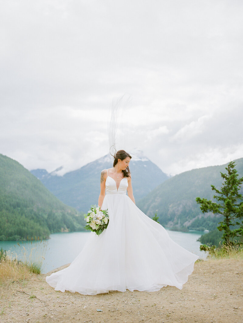 bride looking down over her shoulder as her veil is being swift up by the wind at Diablo Lake in Washington