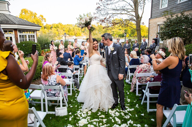 A cheerful bride and groom walking down the aisle at their intimate outdoor wedding ceremony at the Herrington Inn in Geneva, IL.