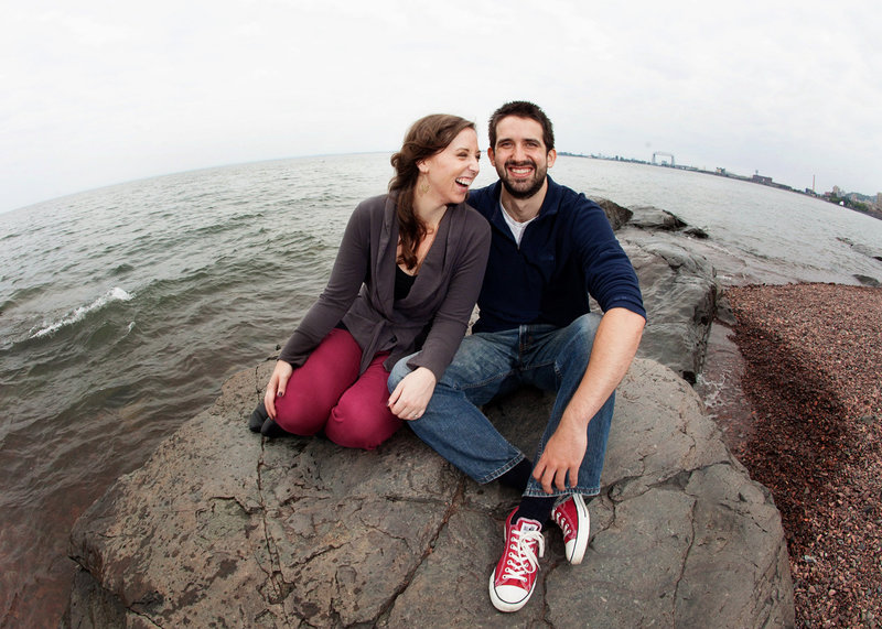 Engaged couple sitting on a large rock at Brighton Beach on North Shore of Lake Superior, Wi.