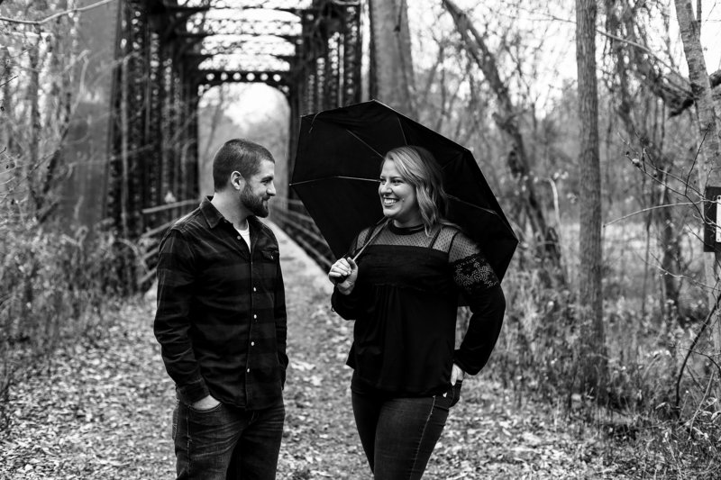 Woman laughs at fiancee while holding umbrella during rainy engagement photo session at the Barn at Conneaut Creek