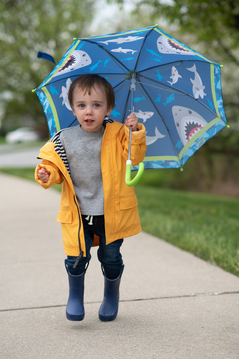 Little boy jumping in yellow raincoat and blue umbrella