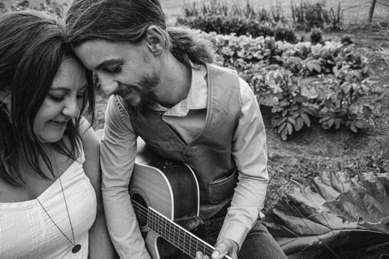 couple leans foreheads together holding a guitar