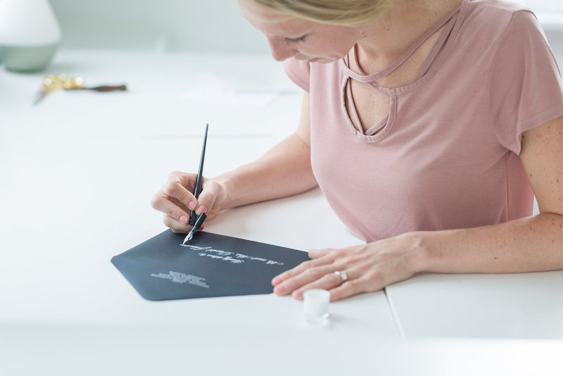 Headshot of Katy Ackerman working on her calligraphy