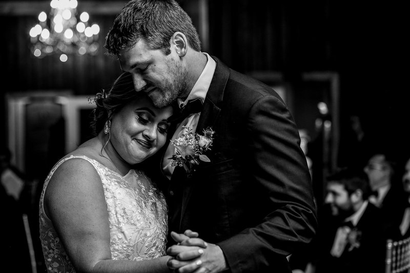 Bride snuggles into groom's shoulder during first dance at Majestic Woods wedding reception