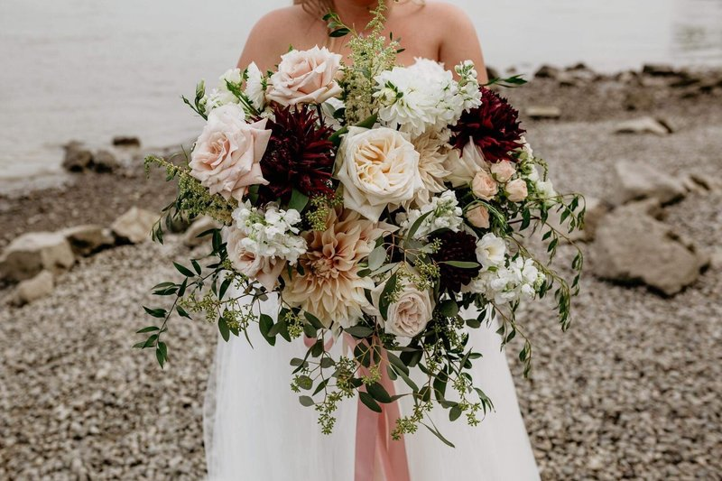 Large blush and burgundy bridal bouquet on beach rocks