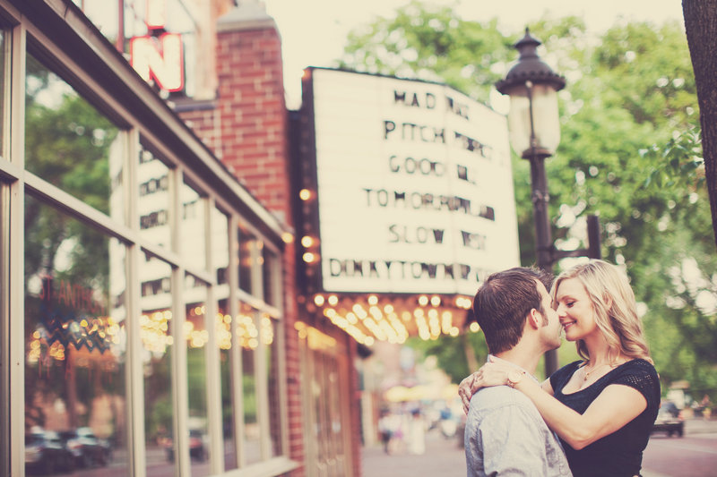 Engaged couple kissing in front of movie theater lights, downtown Minneapolis Minnesota