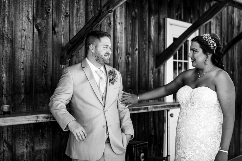 Bride touches groom's arm during first look at Port Farms