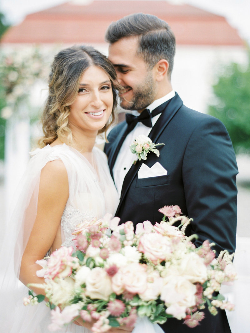 Happy bridal couple smiling, the bride is holding a garden inspired wedding bouquet with light pink roses designed by Stockholm wedding planner, designer and florist Linnéa Bergqvist