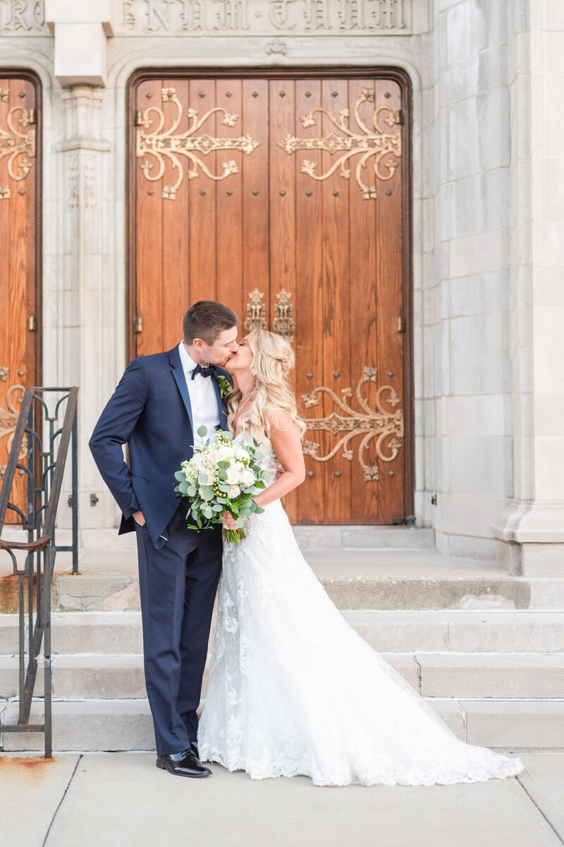 Bride wearing a lace wedding dress and groom wearing a navy tux kissing outside of st cecilia church in hyde park cincinnati ohio