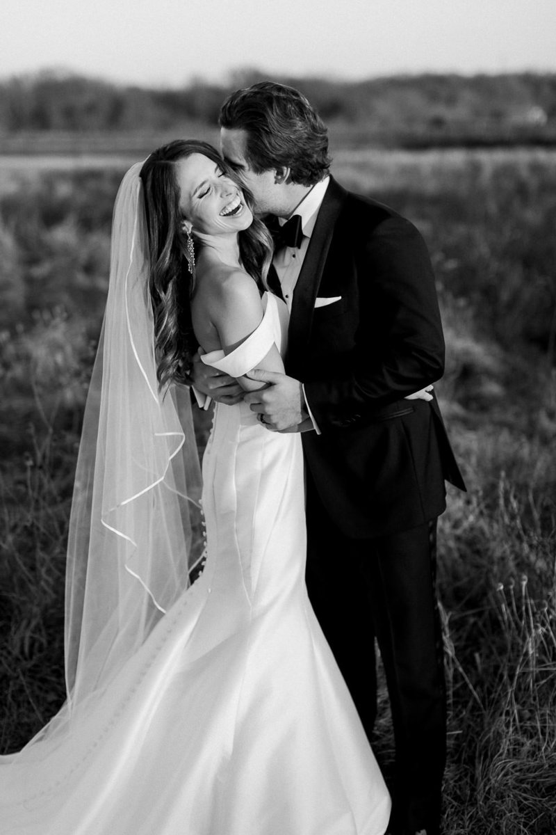 groom embracing bride in wedding dress and veil as she laughs