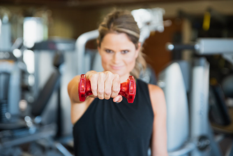stylized lifestyle headshot image of health coach holding red weight out toward camera
