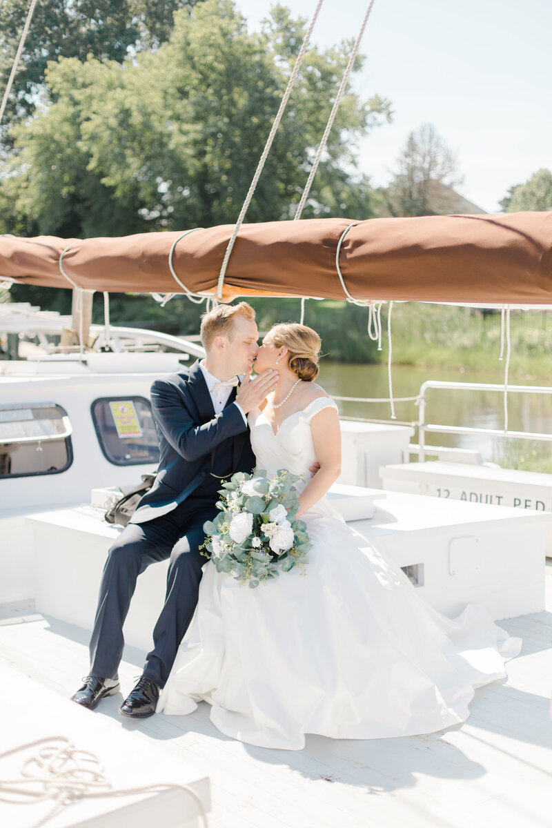 couple on sailboat on wedding day at Inn at Perry Cabin wedding in St Michaels Maryland by Costola Photography