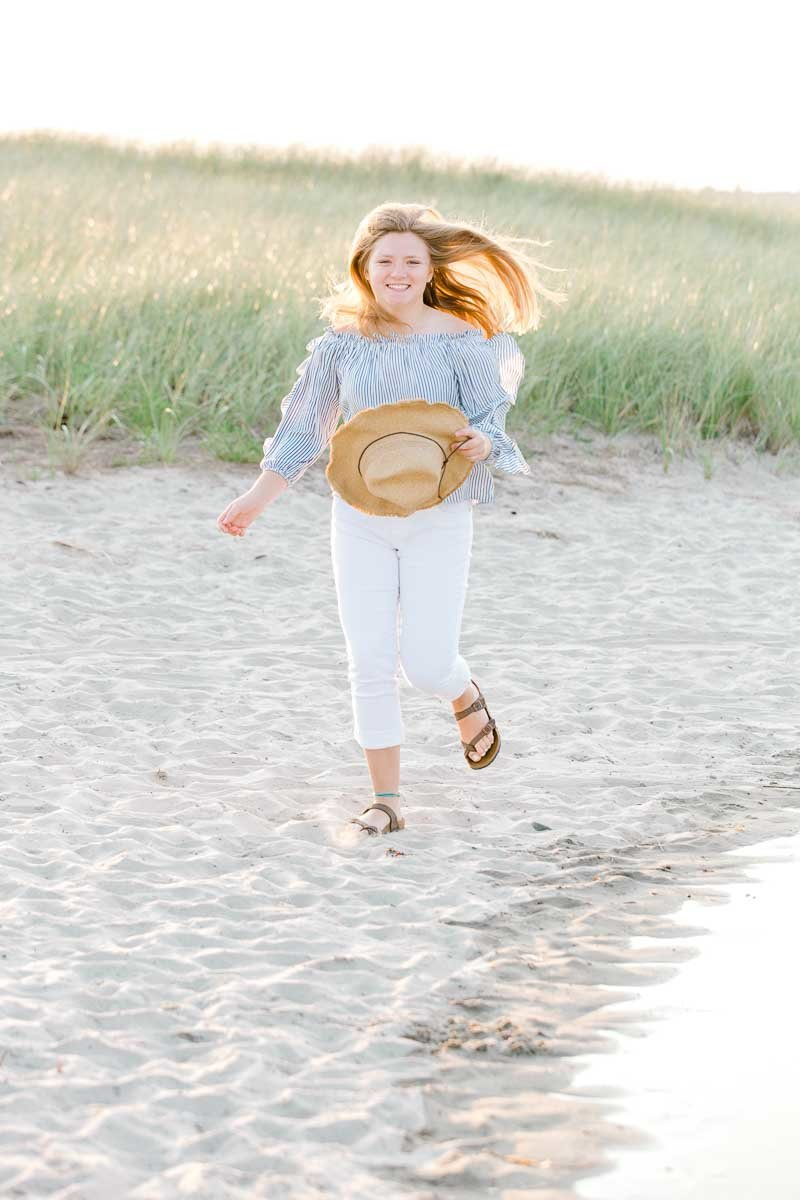 Light and Airy High School Senior portrait.  Candid photo showing a girl wearing running on the beach on Drakes Island in Maine