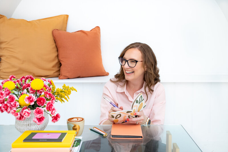 Melissa-Packham_A-Brand-Is-Not-A-Logo_Melissa-sitting-at-coffee-table-with-notebooks-coffee-flowers_look-right-smiling_Landscape