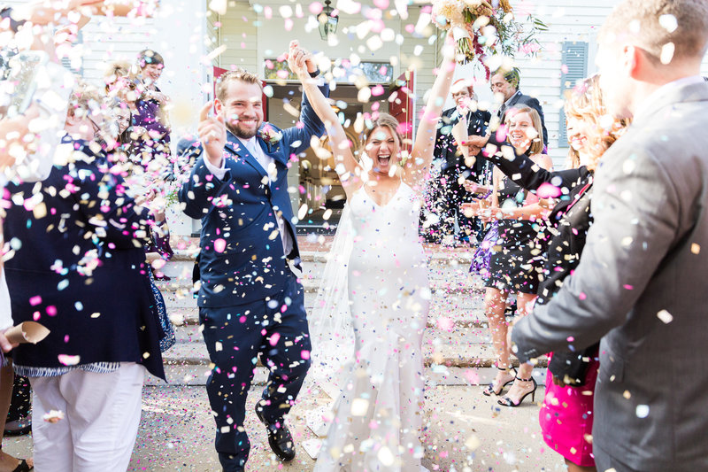 Bride and groom cheer and run through confetti after getting married