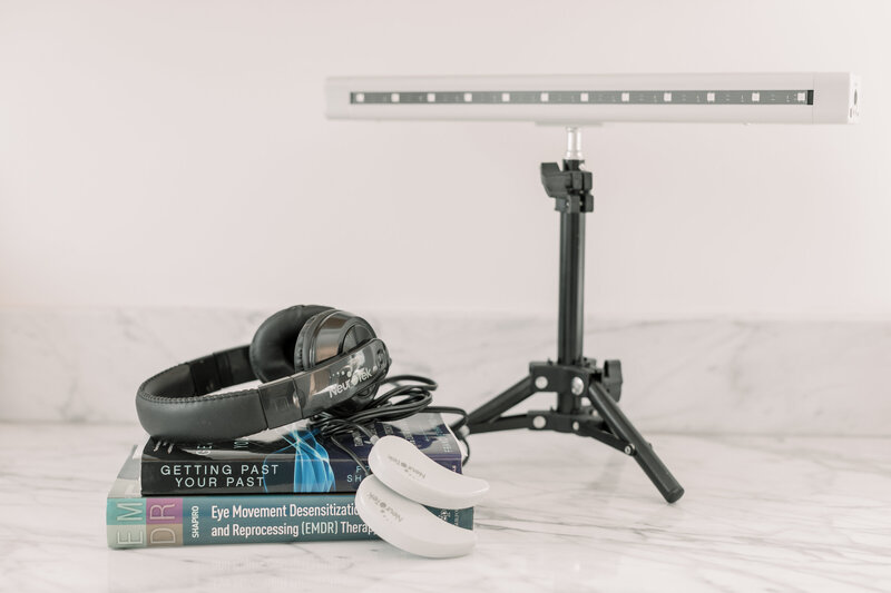 EMDR light bar, two books, headphones and other EMDR therapy tools on a marble tabletop. You can get EMDR therapy in the Los Angeles County area with a skilled EMDR therapist for trauma treatment, vicarious trauma, anxiety and more in Santa Monica, CA and beyond. Learn here about EMDR explained with Santa Clarita therapist, Megan Zuzevich.