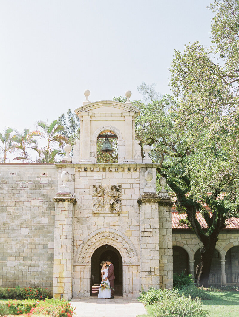 bride and groom under a stone arch at The Acient Spanish Monastery in Miami Florida