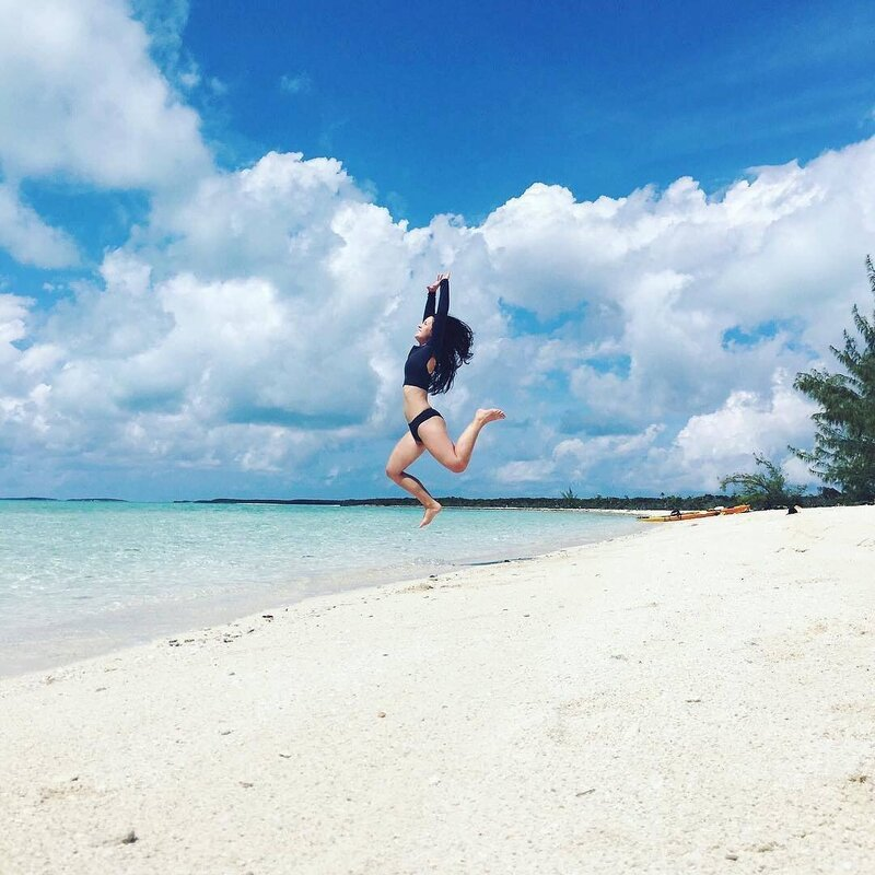 Dani jumpin on beach in Exuma