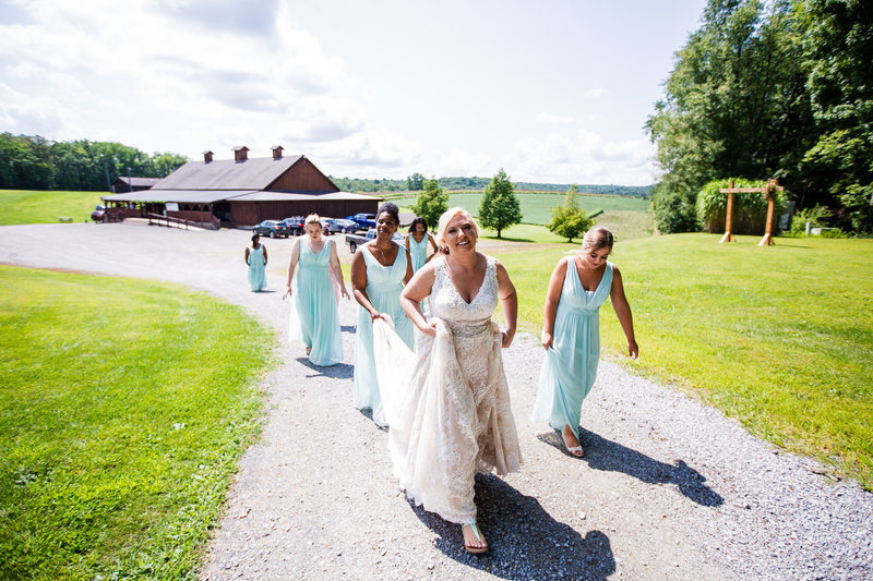 Bride walks the path with her bridesmaids at her Betsy's Barn wedding