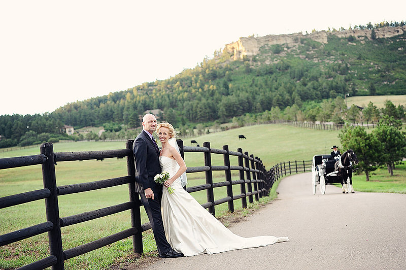 couple leaning against fence at Spruce Mountain Ranch
