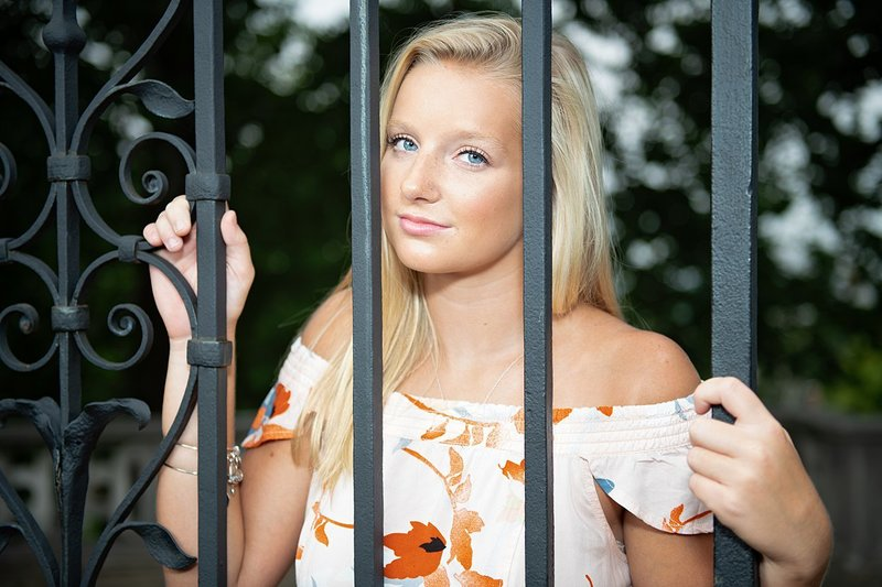 High school senior girl in off the shoulder flowered dress looking through the bars of a wrought iron gate at Mellon Park in Pittsburgh, PA