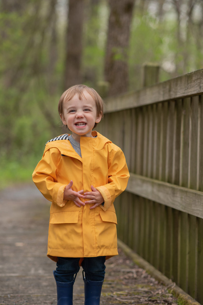Little boy on bridge in yellow raincoat