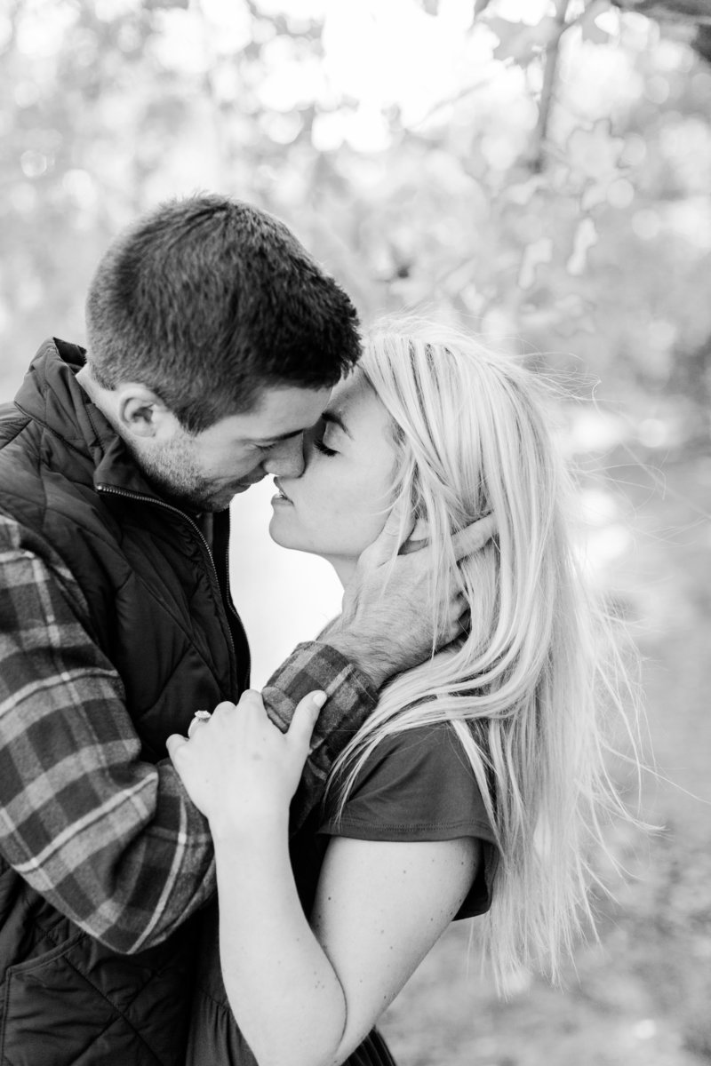 Engagement photo of couple  kissing in the woods