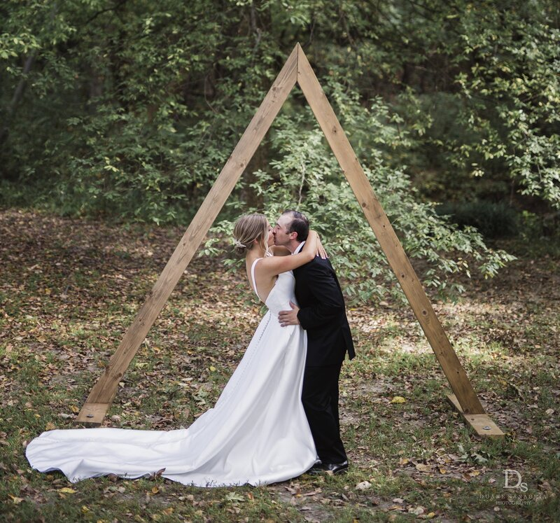 Simple woods wedding with triangle arbor