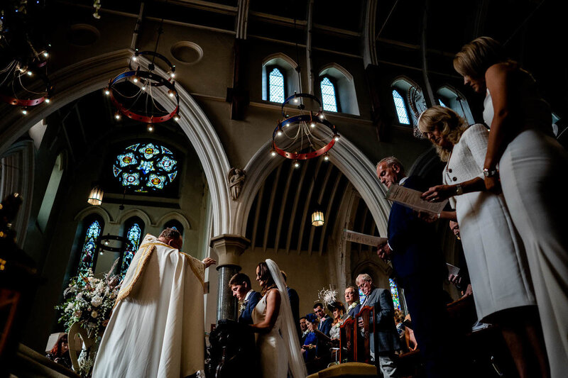 vicar gives his wedding blessing to a bride and groom