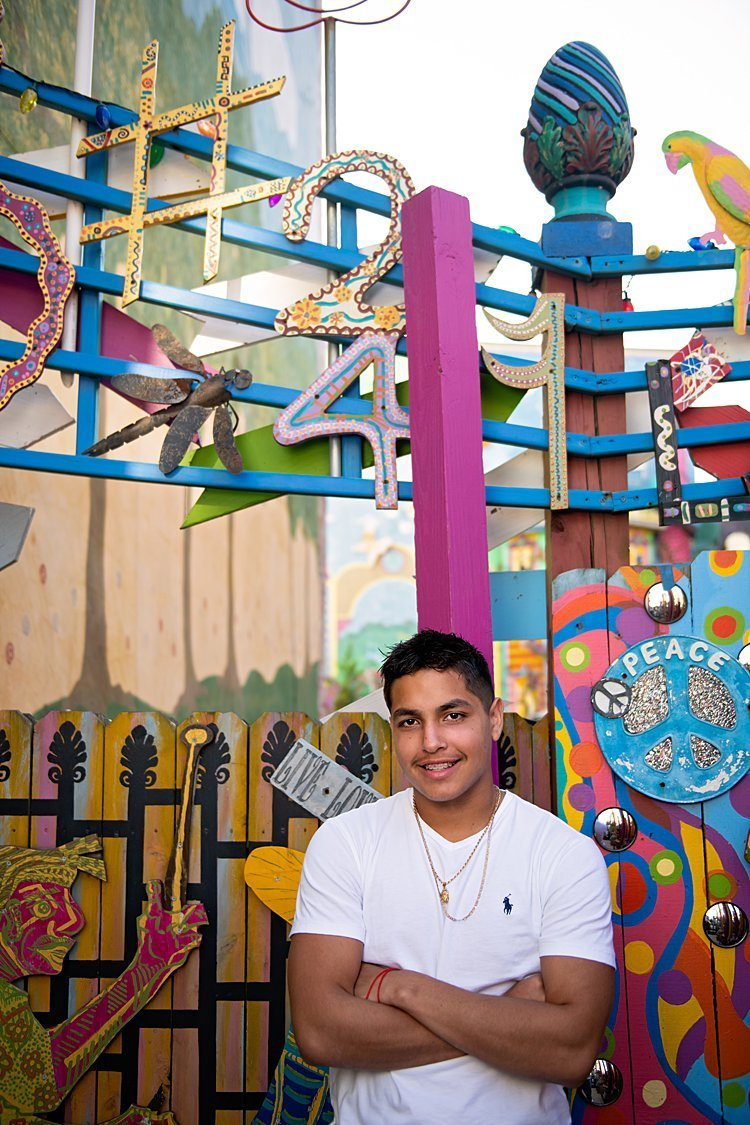 High school senior boy in white Polo tee leaning against pink post with colorful fence at Randyland in Pittsburgh, PA