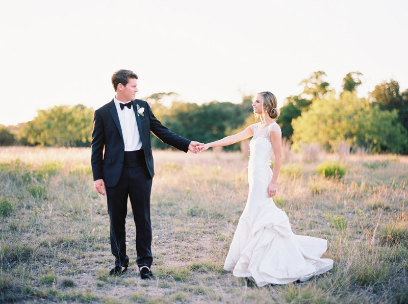 Groom and bride hold hands in field